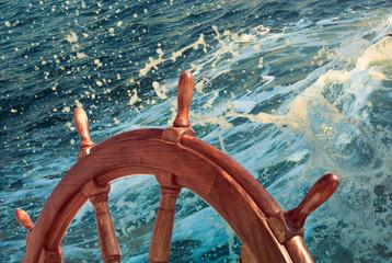 Wooden steering wheel at sea background