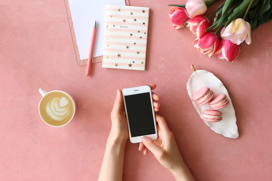 Top view shot of woman hands holding blank screen cell phone, concrete textured table background. Feminine workspace with flowers bouquet. Close up, copy space.