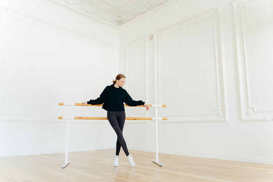 Classic ballet dancer has stretching workout, stands near ballet barres, wears black sweatshirt and leggings, does exercises in studio, focused down. Certified female instructor of choreography