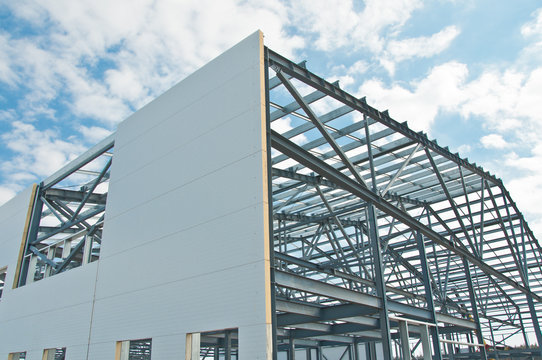 Metal frame of the building with a sandwich panel of insulation on the wall. Construction of a new industrial building.