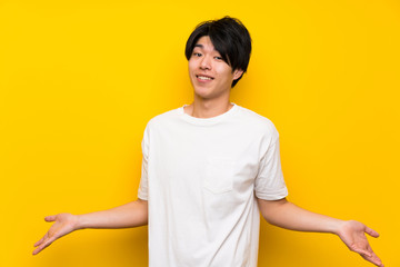 Asian man over isolated yellow wall smiling