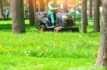 Papiers peints Vert chaux Professional lawn mower with worker cut the grass in a park