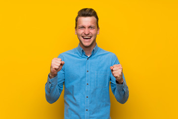 Blonde man over isolated yellow wall celebrating a victory in winner position Wall mural