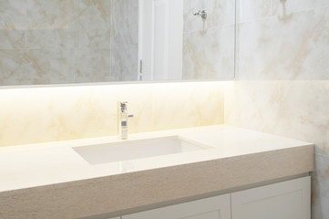 Counter top white,beige marble with washbasin. Wall and floor beige marble stone interior design of restroom or toilet background. Restroom clean design with accessories background. Selective focus. Fototapete