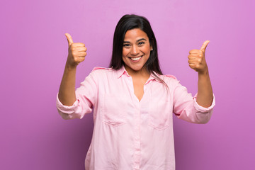 Young Colombian girl over purple wall with thumbs up gesture and smiling Wall mural