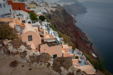 Tilt shift effect of houses over red cliffs in the village of Oia