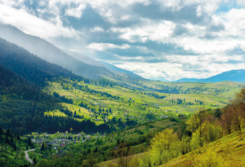 road through the village in valley of Carpathians. lovely springtime scenery in mountains of Synevyr National park
