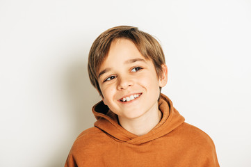 Studio shot of handsome 10 year old boy with blond hair, wearing brown hoody, posing on white...