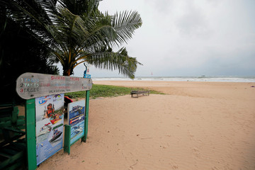 An empty beach is seen near a sign of the boat safari and whale watching center in a tourist area in Bentota