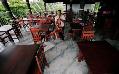 A man arranges chairs at an empty restaurant of the Warahena Beach hotel in Bentota