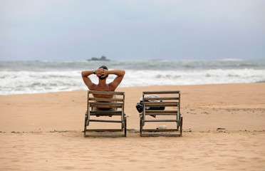 A tourist rests on a beach near hotels in a tourist area in Bentota