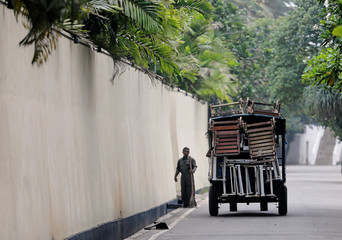 A tractor transports sunbathing chairs from a hotel on a road towards tourist area in Bentota