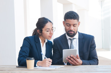 Business people using tablet and working at wooden desk. Business man and woman wearing formal clothes and sitting at cafe table. Business work concept. Front view.