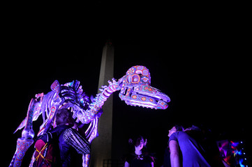 A replica of dinosaur skeletons is illuminated in front of the Washington Monument as people enjoy a festival event called 'Catharsis on the Mall' in Washington