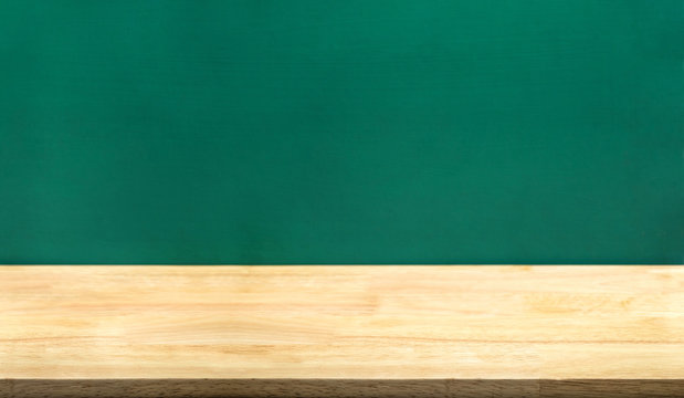 Empty wood table and green blackboard at background.education school concept product display template.Business presentation..
