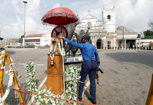 A Sri Lankan navy personnel places a flower garland on a statue of St. Anthony, in front of St. Anthony's Shrine, where an explosion took place during mass on Easter Sunday, in Colombo