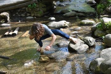 Barefoot boy exploring stream or creek Wall mural