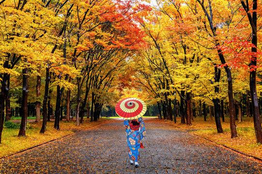 Asian woman wearing japanese traditional kimono walking in autumn park.