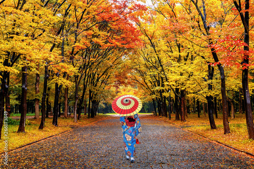 Wall mural Asian woman wearing japanese traditional kimono walking in autumn park.