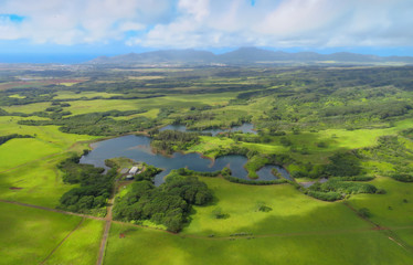 Lihue, aerial helicopter view over pond and green meadows, Kauai, Hawaii, USA