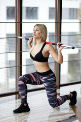 Pretty blonde woman doing squats with barbell in fitness hall. Active Lifestyle. Sports in the gym.