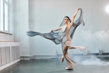 Female ballet dancer with white flowing fabric. Flow shapes and movement in the studio on white smoky background.