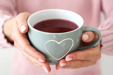 Woman s hands holding big mug with heart .
