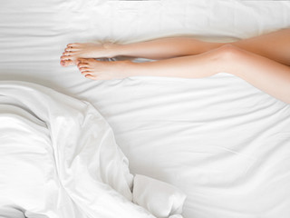 Poster Spa long slim female legs on the white sheets. Close Up Of Female With Perfect Healthy Silky Legs Skin After Hair Removal On White Bed In Light Interior. Beauty, Skin Care Concept.
