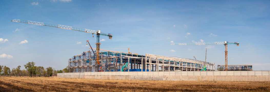 panorama construction site background. industrial background. structural steel beam build large residential buildings at constructions site . crane and building site on blue sky