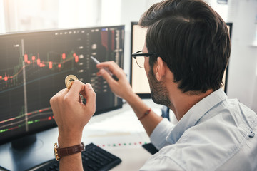 Exchange stock market. Back view of young professional trader in eyeglasses pointing on the data on computer screen with pen and holding Bitcoin in one hand while working his modern office.