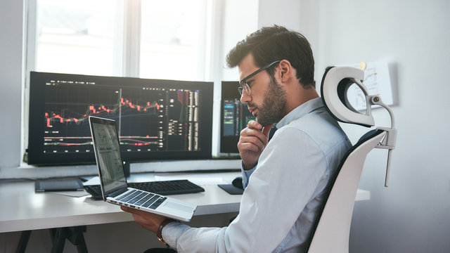 Busy day. Professional male trader wearing eyeglasses analyzing financial market via laptop while sitting in front of computer screens with trading charts in modern office interior