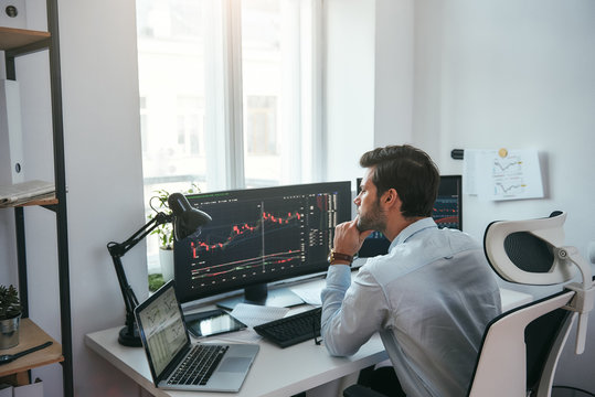 Trading on world markets. Young stock market broker analyzing data and graphs on multiple computer screens while sitting in modern office