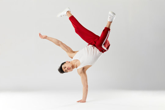 Athletic young b-boy standing on one hand while dancing break dance and doing downrock isolated over white studio background.