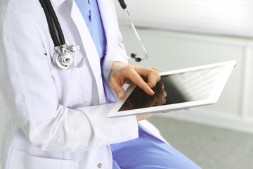 Woman doctor using white tablet computer while working in clinic. Medicine and health care concept