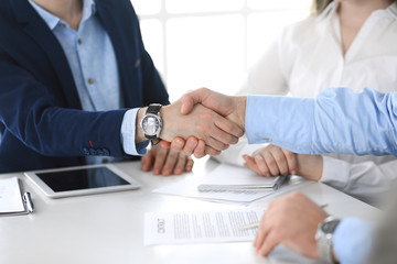 Business people shaking hands at meeting or negotiation, close-up. Group of unknown businessmen and women in modern office. Teamwork, partnership and handshake concept