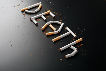 The inscription DEATH from cigarettes on a black background. Stop smoking. The concept of smoking kills. Motivation inscription to quit smoking, unhealthy habit.