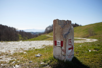 European path E5 with stone cippus and panorama of the mountains in the background