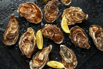 Fresh Oysters platter with lemon and ice. ready to open and eat