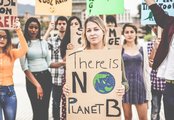 Group of demonstrators on road, young people from different culture and race fight for climate change - Global warming and enviroment concept - Focus on blond girl face Wall mural