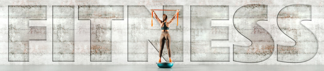 Full length of sporty woman standing on bosu ball and holding ribbon. Back turned, in background gray wall. Upper-case fitness over the picture.