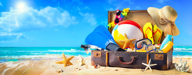 Beach accessories in suitcase on sand. Family holidays concept Fotomurales
