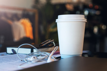 Closeup of a white paper cup of coffee on a table in an empty cafe without people. Nearby are the headphones and notebook. Mockup.