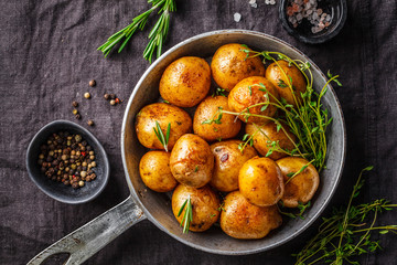 Baked potatoes in a cast iron skillet, dark background.