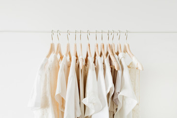 Fototapeta Minimal fashion clothes concept. White female blouses and t-shirts on hanger on white background. obraz