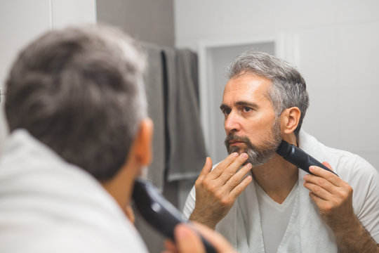 middle aged bearded gray haired man trimming his beard in bathroom