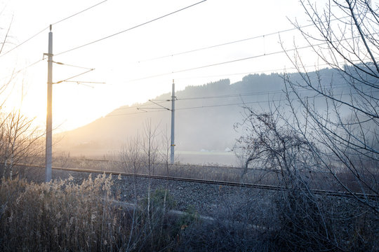 sunset in a foggy mystic scenery with small bushes and train tracks with power lines in styria