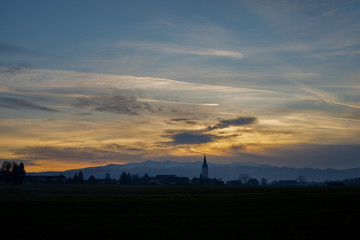 Autocollant pour porte Cracovie colorful sunset with different types of clouds and a hill and valley silhouette with a church tower in the austrian alps in styri