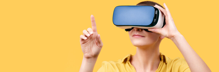 Young woman in her 30s using virtual reality goggles. Woman wearing VR headset isolated over yellow banner. VR experience concept.