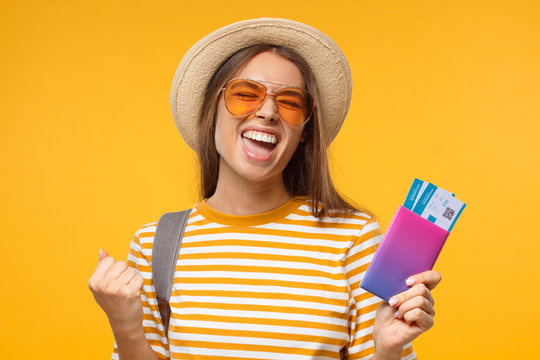 Tourism concept. Excited young female tourist celebrating if she is a winner, holding passport with flight tickets, isolated on yellow background