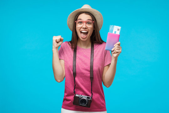 Close-up portrait of young female tourist with flight tickets screaming if she is a winner, isolated on blue background